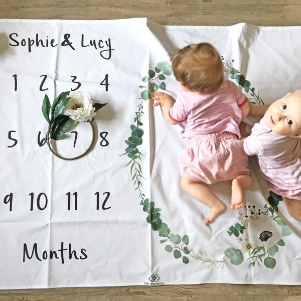 Meilensteindecke mit Blumenkranz und Monatskalender für das erste Jahr, hier gezeigt, wie das Alter zweier Kleinkinder mit einer Kunstblume markiert wird, während die Kinder für das Foto im Muster posieren