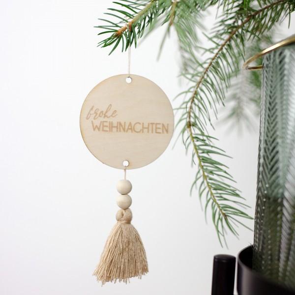 Anhänger Frohe Weihnachten mit einer beigen Quaste an einem Tannenzweig hängend