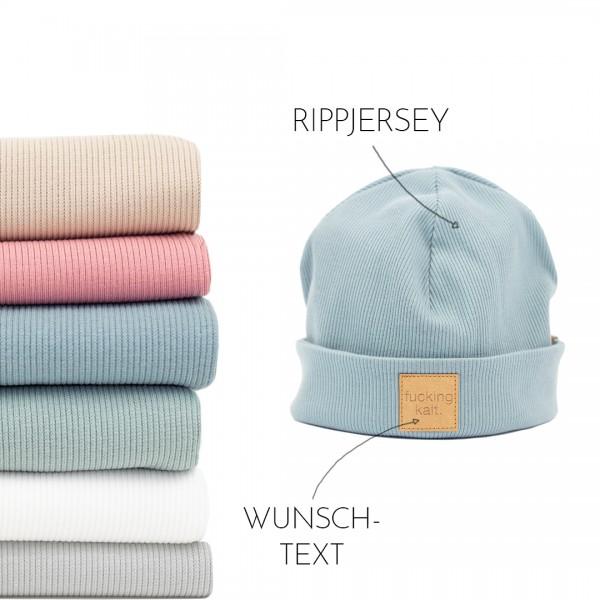 Mütze mit Umschlag in der Farbe hellblau mit personalisierbaren Text und ein Stappel mit den Rippjersey Farben.