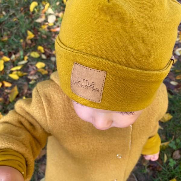 """Tragebild Kind mit senffarbener Beanie mit Aufschrift """"little monster"""" und farblich passender walkjacke"""