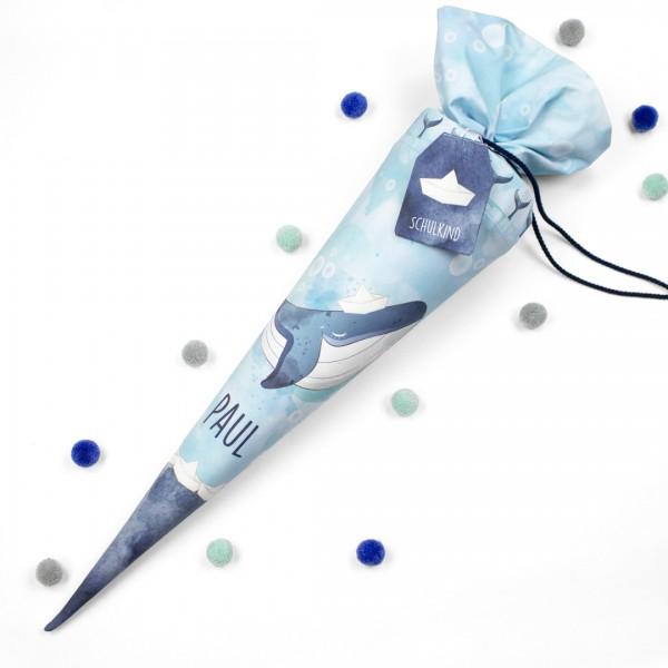 Blaue Schultüte mit Wal Print, der Wal trägt ein Papierschiff auf dem Kopf, die Tüte ist oben zugebunden
