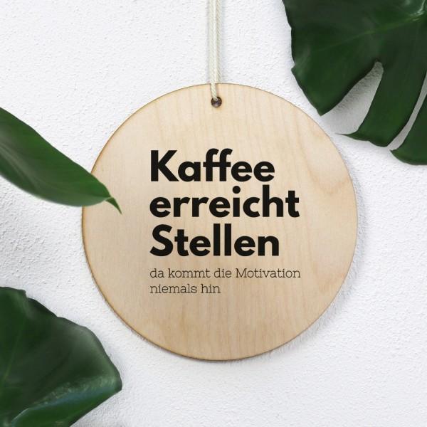 """Holzschild bedruckt mit Aufschrift """"Kaffee erreicht Stellen da kommt die Motivation niemals hin"""" mit Pflanzendeko"""