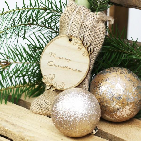 """Holzanhänger mit Schrift """"Merry Christmas"""" vor Weihnachtsdeko"""
