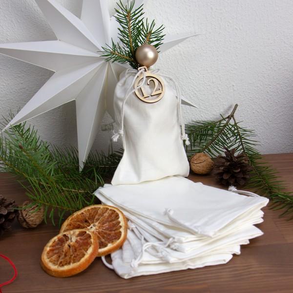 Weiße Adventskalender Säckchen dekoriert mit Holz Anhänger Weihnachtskugel zwischen getrockneter Orange und Tannenzweigen