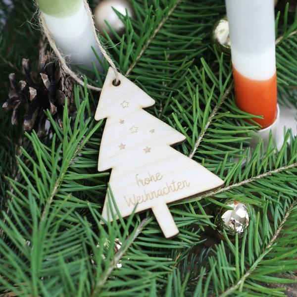 Holzanhänger Weihnachtsbaum mit Frohe Weihnachten Schrift neben Weihnachtsdeko