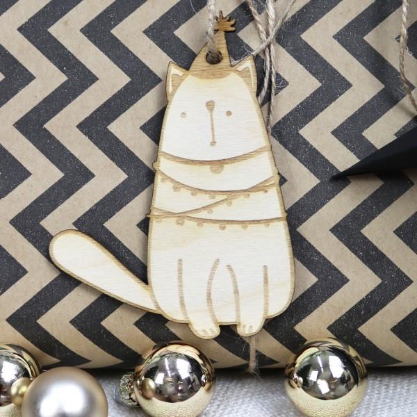Holzanhänger Katze mit Partyhut und umwickelt mit einer Lichterkette vor Geschenk