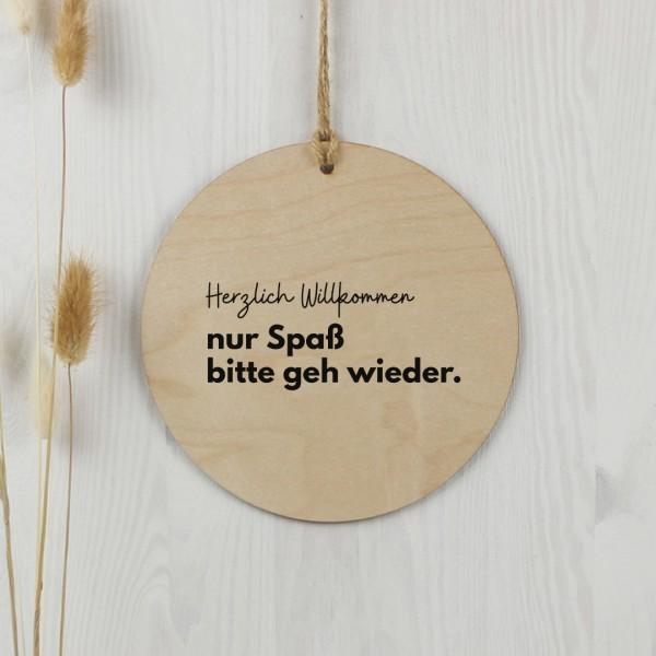 """Holzschild bedruckt mit Aufschrift """"Herzlich Willkommen nur Spaß bitte geh wieder."""" und Pflanzendeko"""