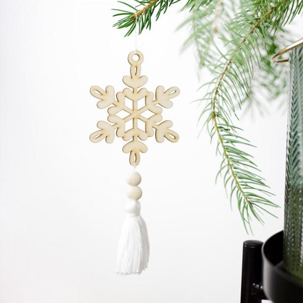 Anhänger Schneeflocke mit einer weißen Quaste an einem Tannenzweig hängend
