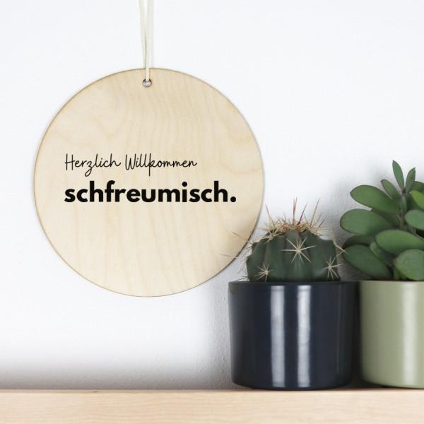 """Holzschild bedruckt mit Aufschrift """"Herzlich Willkommen schfreumisch"""" und Pflanzendeko"""