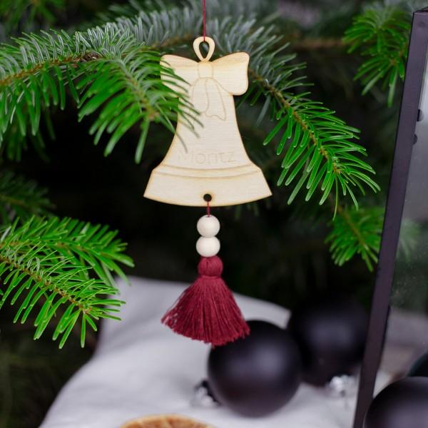 Anhänger Glocke mit roter Quaste an einem Tannenzweig hängend mit Wunschname Moritz
