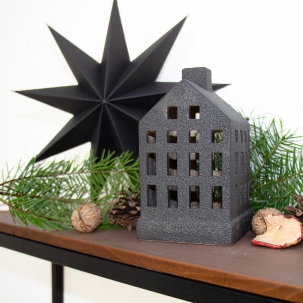 Windlicht   Haus   schwarz   klein mit Tannenzweigen und Stern im Hintergrund